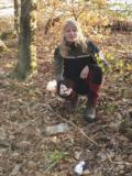 knieende blondhaarige Försterin Wald mit Müll in den Händen, den sie in die Kamera hält